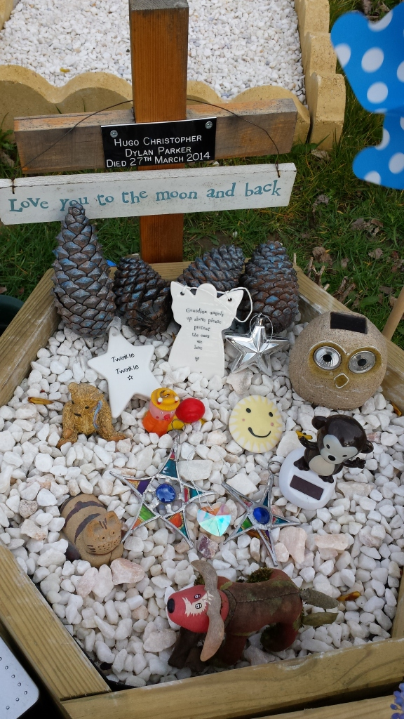 Toys, mementoes, and sparkly stones in the hexagonal planter.